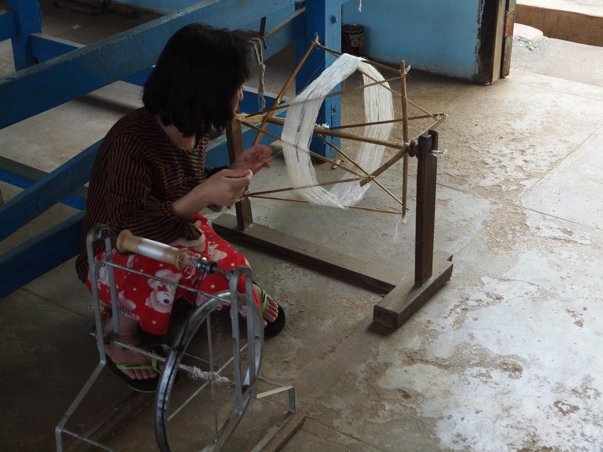 ミャンマーのある作業場でシルクの糸をつむぐ